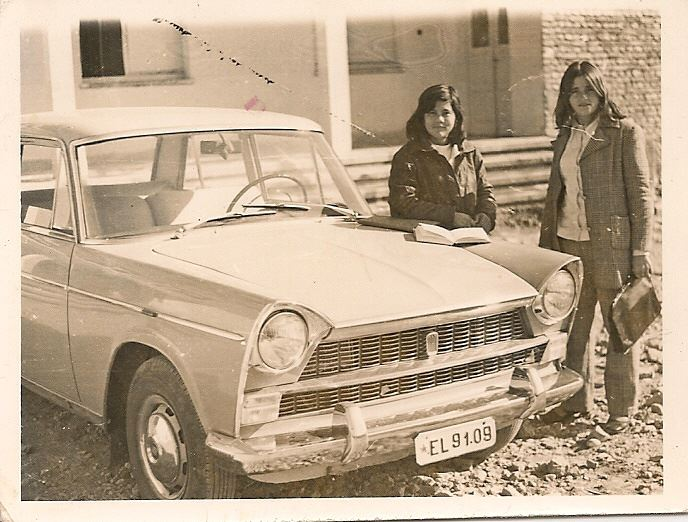 Two women stand next to a car
