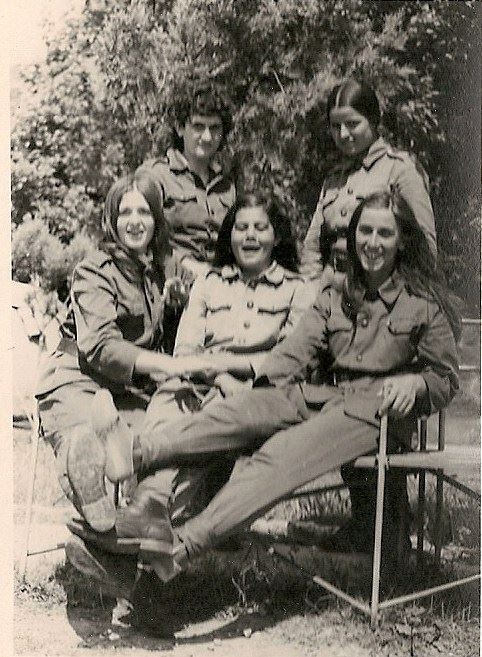 five women sit close together